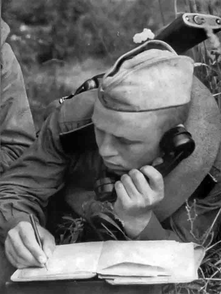 Soviet soldiers signalman receives a telephone message from command
