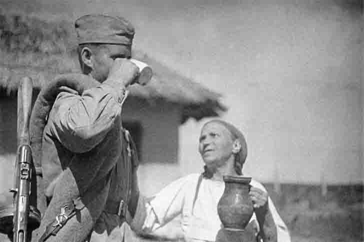 Romanian peasant woman treats milk to a Soviet soldier