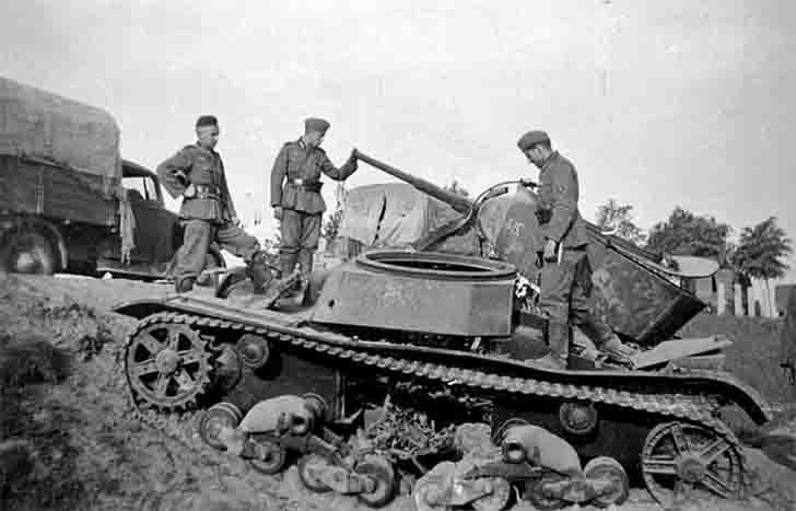 Three German soldiers inspect the broken T-26 light tank