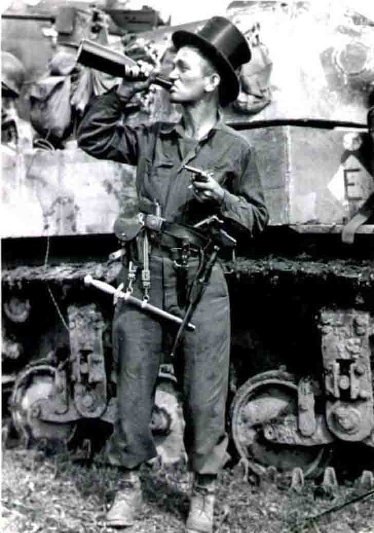 American soldier posing with captured weapons, a bottle and a hat-cylinder