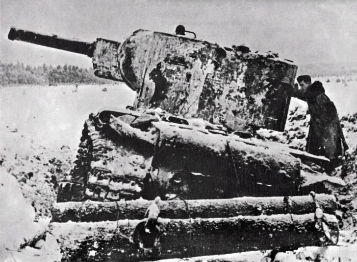 A German soldier inspects a damaged Soviet KV-2 tank