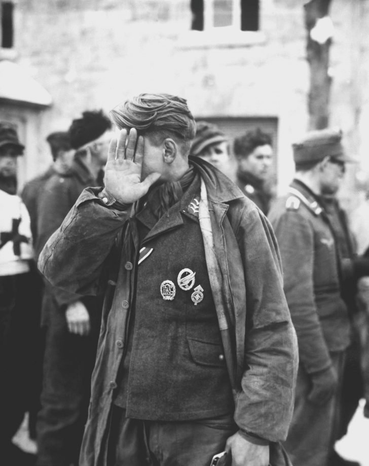 Luftwaffe prisoner of war in Weywertz trying to hide his face from the photographer