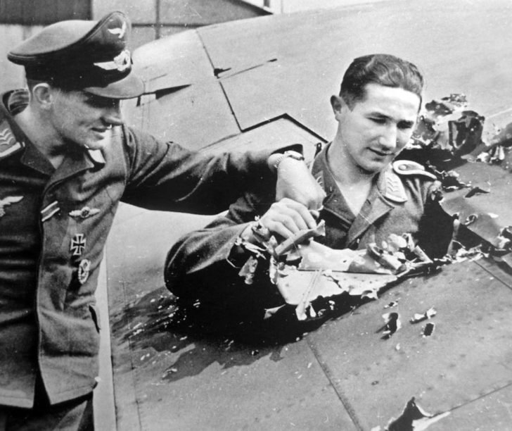 German pilots inspect the hole in the wing of the aircraft